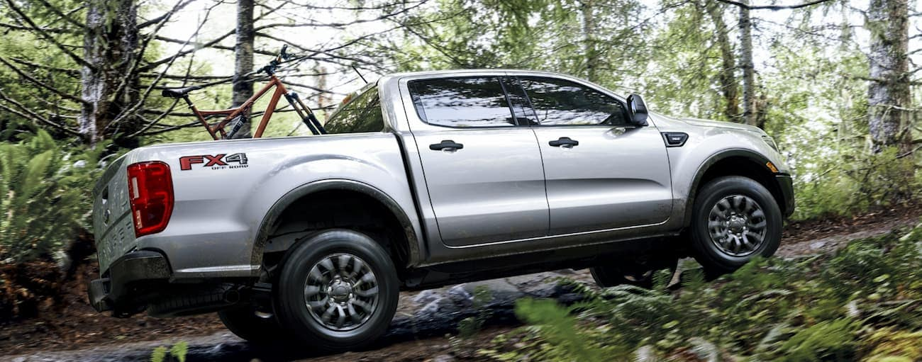 A silver 2020 Ford Ranger XLT is driving on a dirt trail through the woods.