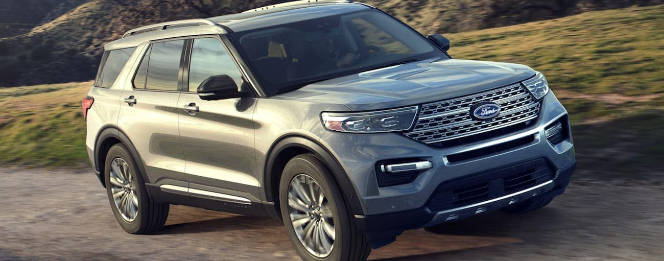 A silver 2020 Ford Explorer is driving up a hill on a dirt road.