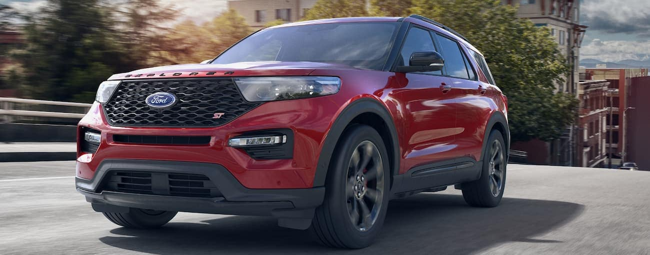 A red 2020 Ford Explorer ST, which wins when comparing the 2020 Ford Explorer vs 2020 Honda Pilot, is driving on a bridge near Cincinnati, OH.