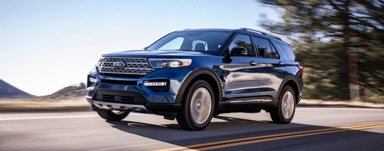 A blue 2020 Ford Explorer is driving on a road with hills in the distance.