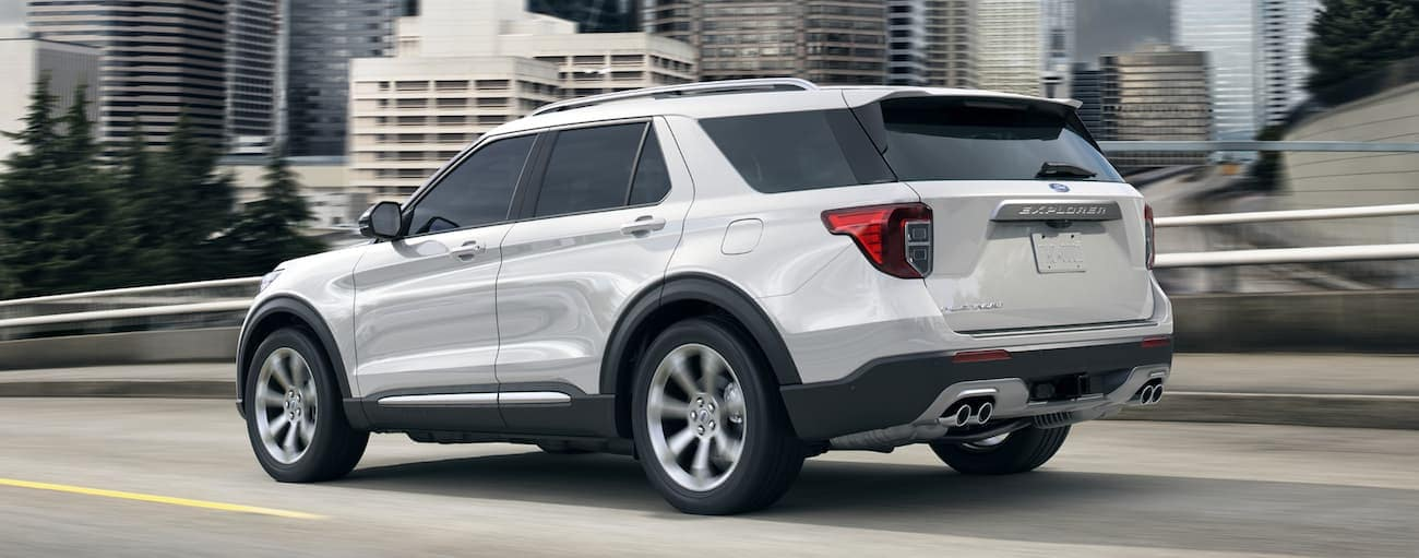 A white 2020 Ford Explorer, which wins when comparing the 2020 Ford Explorer vs 2020 Toyota Highlander, is driving on a bridge near Cincinnati, OH.