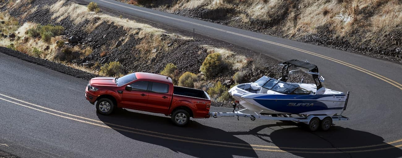 A red 2020 Ford Ranger, which wins when comparing the 2020 Ford Ranger vs 2020 Chevy Colorado, is towing a boat up a hill near Cincinnati, OH.