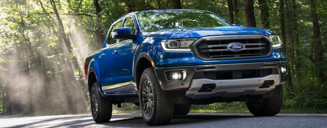 A blue 2020 Ford Ranger is driving on a shaded treelined road near Cincinnati, OH.