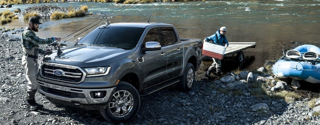 Two fisherman are unpacking their trailer that was towed by a 2020 Ford Ranger, while standing next to a lake.