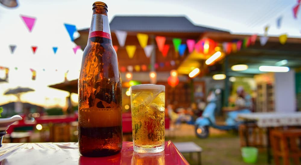 A home brewed bottle of beer is sitting on a picnic table with festival lights in the distance.