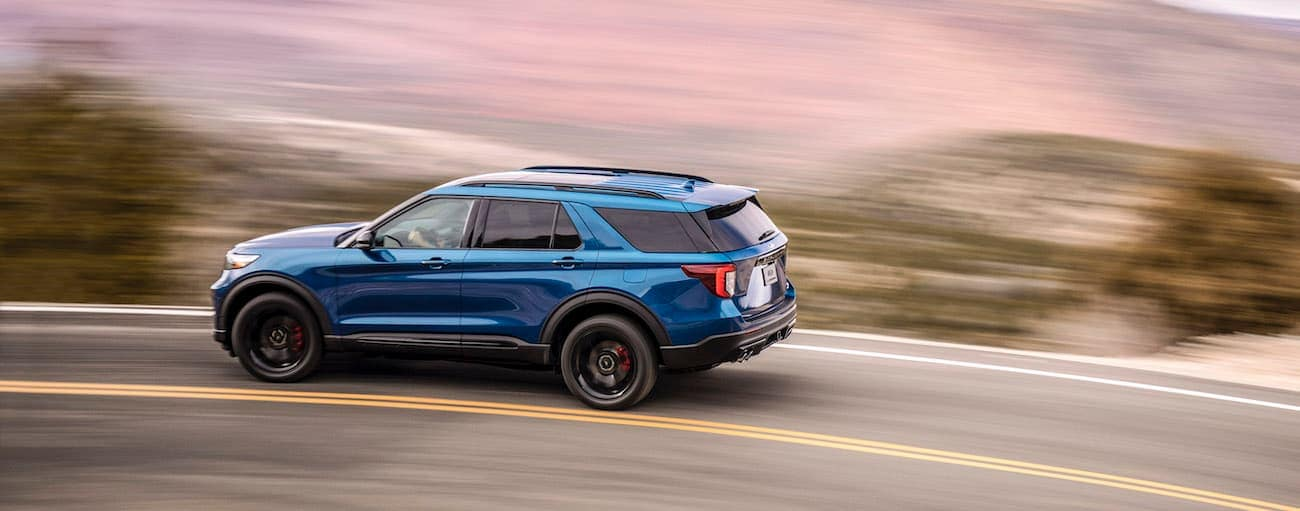 A blue 2020 Ford Explorer, which wins when comparing the 2020 Ford Explorer vs 2020 Jeep Grand Cherokee, is driving on a curved road with a blurred background.
