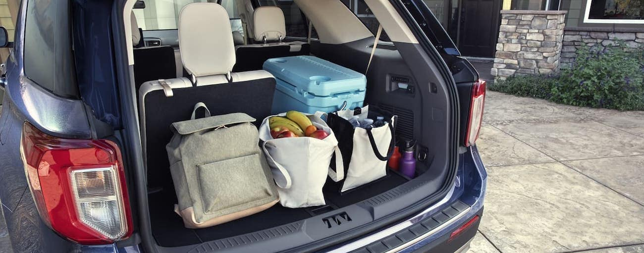 A view of the cargo area of a blue 2020 Ford Explorer filled with luggage and groceries.