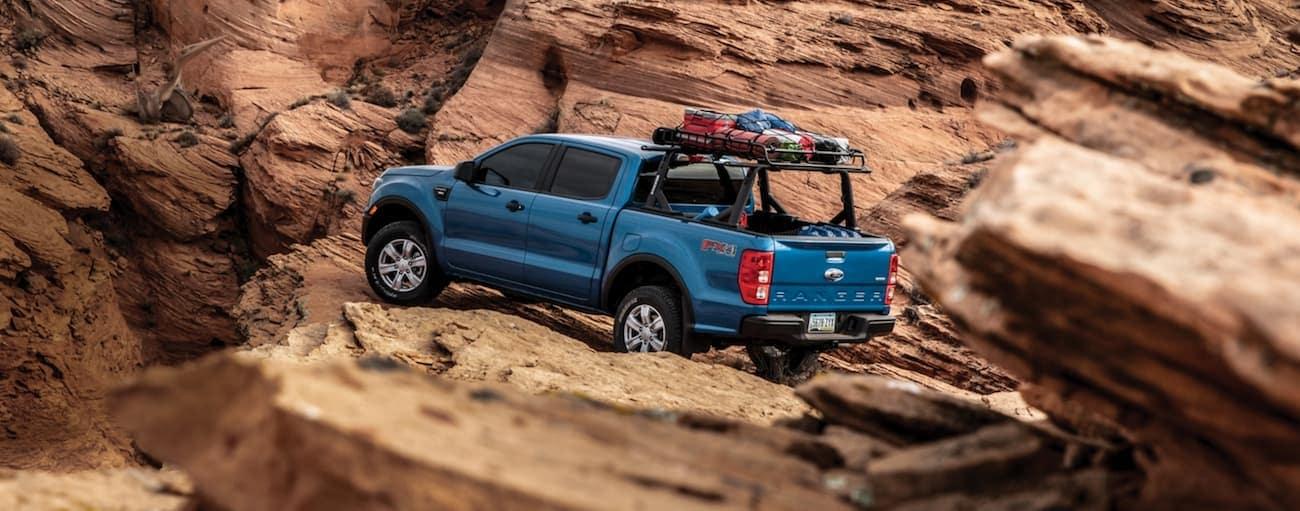 A blue 2020 Ford Ranger is shown off-roading on desert rocks.