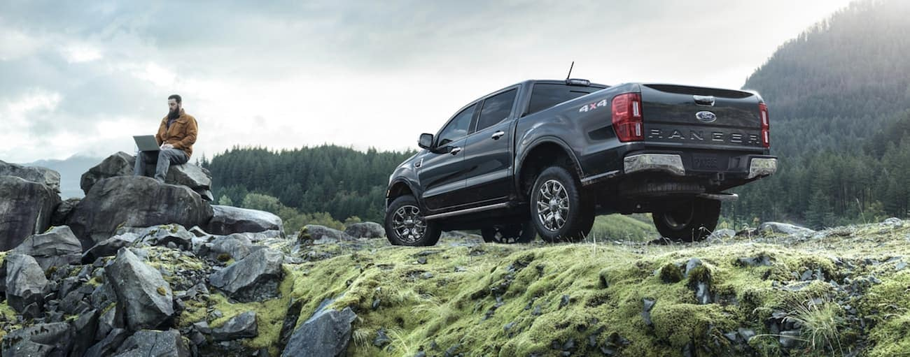 A man is sitting on a rock near his dark grey 2020 Ford Ranger parked on grass.