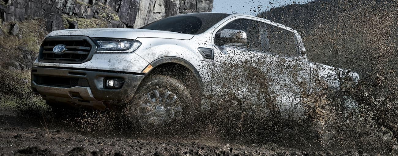 A white 2020 Ford Ranger, which wins when comparing the 2020 Ford Ranger vs 2020 Jeep Gladiator, is spraying mud off-road near Cincinnati, OH.