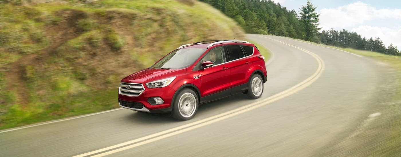 A popular Ford Certified Pre-Owned model, a red 2018 Escape is driving on a winding road.