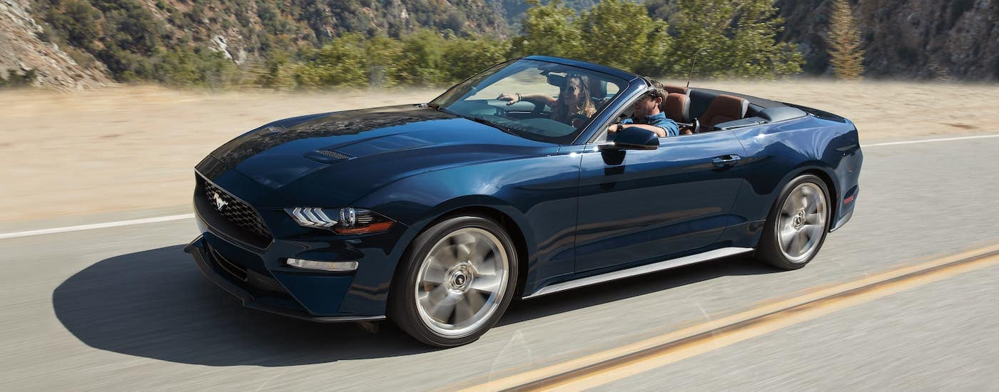 A certified pre-owned 2019 Mustang convertible is driving on a highway.