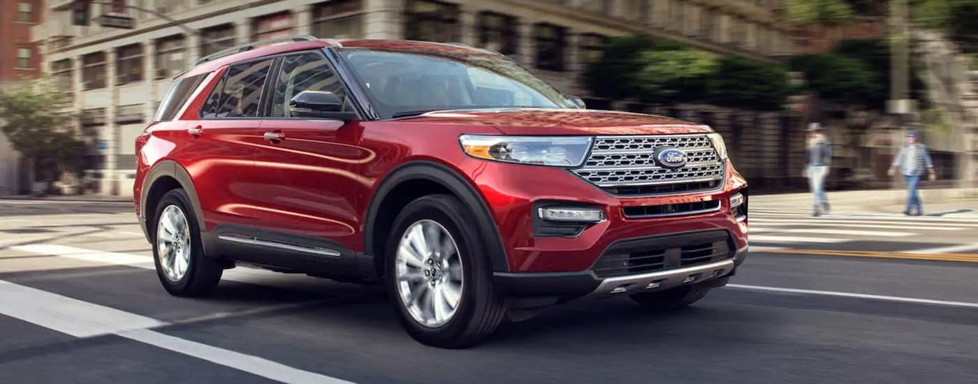 A red 2020 Ford Explorer is driving on a city street after leaving a Ford dealer in Ohio.