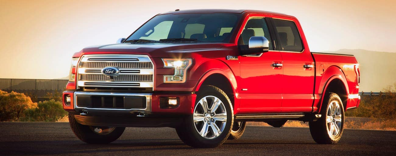 A red 2015 Ford F-150 is parked in an empty lot at sunset.