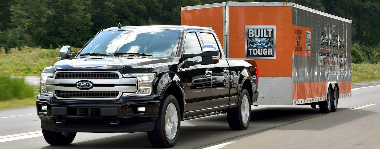 A black 2018 Ford F-150 is towing an enclosed trailer on a highway.