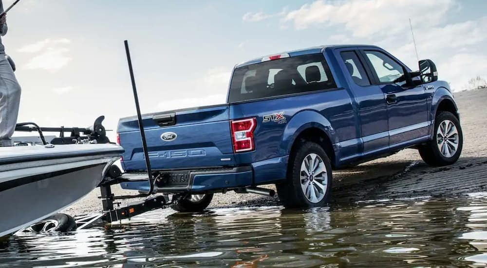 A blue 2020 Ford F-150 is backing a boat into the water near Cincinnati, OH.