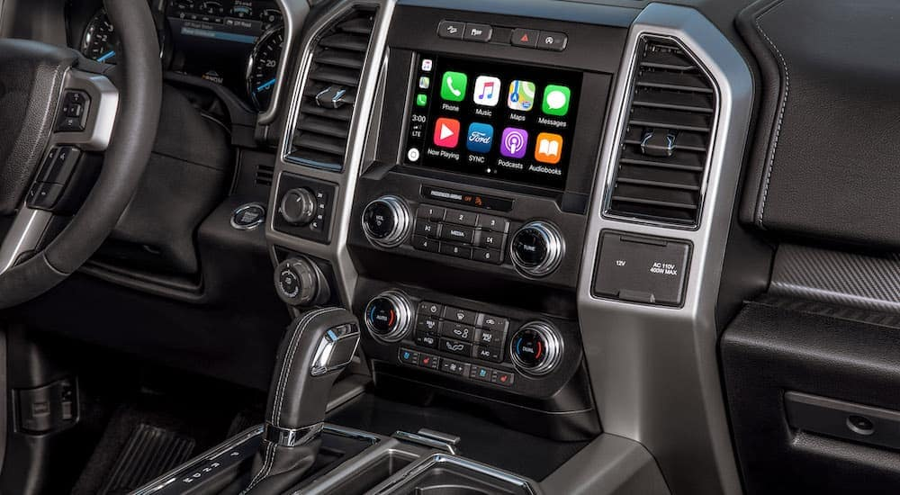 The black interior and infotainment features of the 2020 Ford F-150 Lariat are shown.
