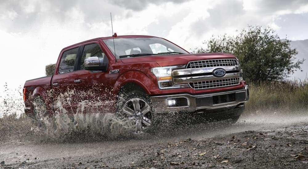 A red 2020 Ford F-150 Lariat, which is popular among Ford trucks for sale, is driving in the mud.