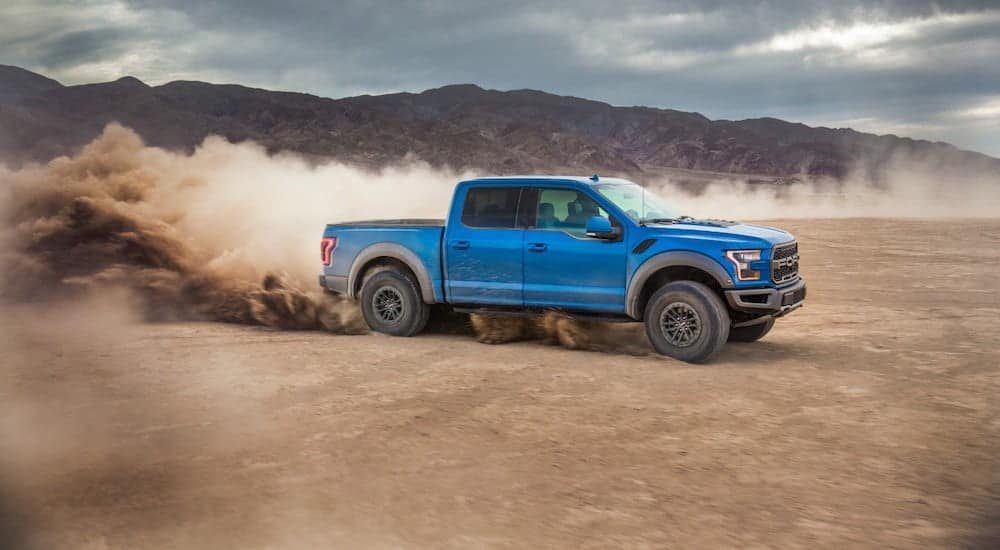 A blue 2020 Ford F-150 Raptor, which is popular among Ford trucks for sale, is driving off-road with a cloud of dust kicking up.
