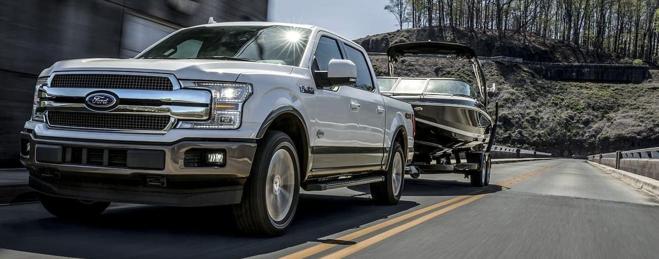 One of the popular Ford Trucks For Sale in Cincinnati, OH, a white 2020 Ford F-150 is towing a boat on a highway.
