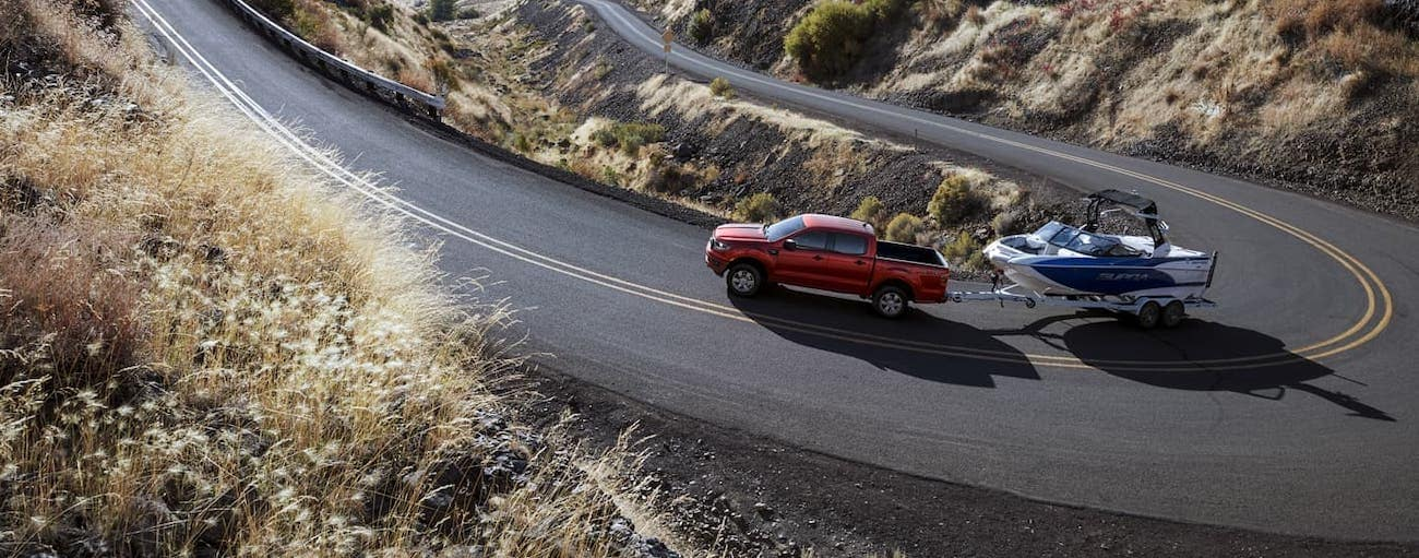 A red 2020 Ford Ranger is towing a boat on a winding road outside Cincinnati, OH.