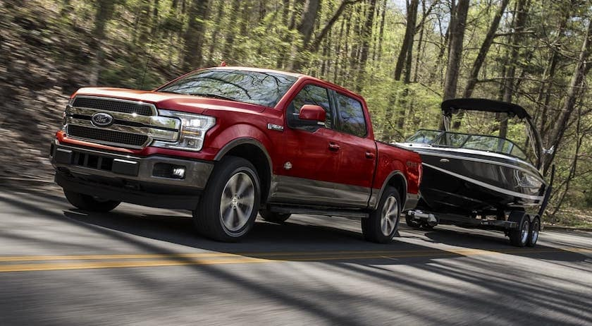 A red 2020 Ford F-150 is towing a boat on a woodland road outside Cincinnati, OH.