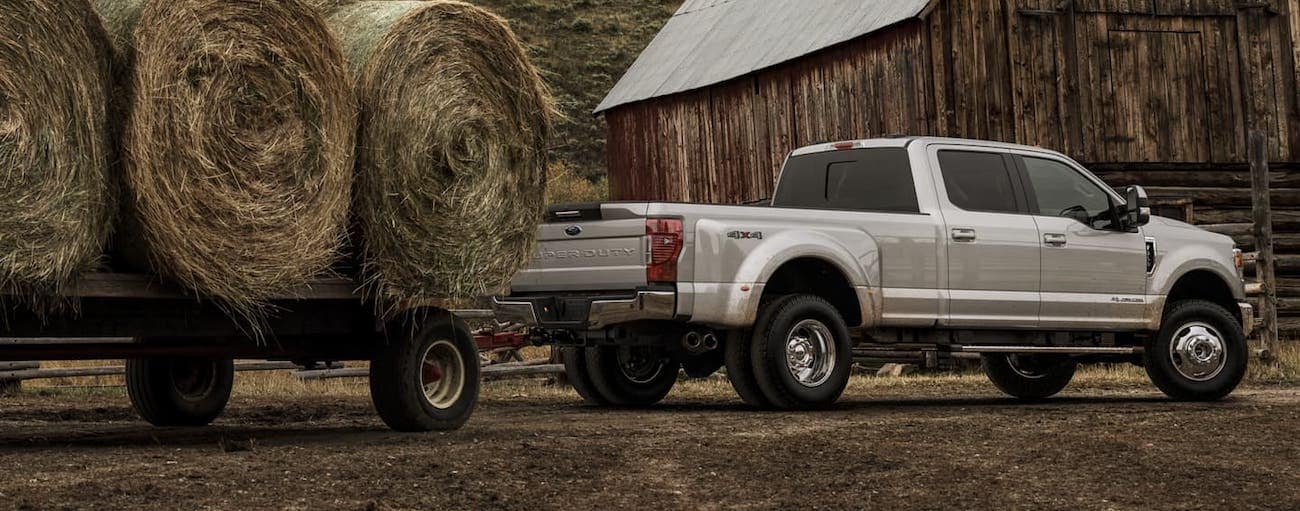 One of the popular Ford Trucks For Sale in Cincinnati, OH, a silver 2020 Ford Super Duty is towing rolls of hay in front of a barn.