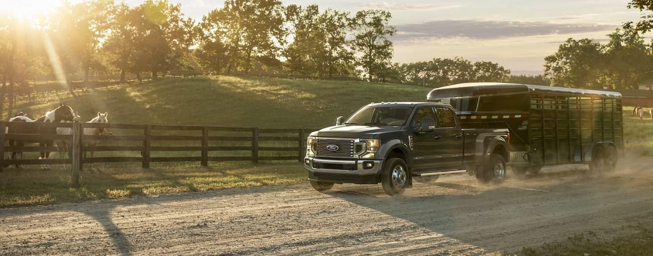 A black 2020 Ford Super Duty is towing a trailer in front of a horse farm at sunset.