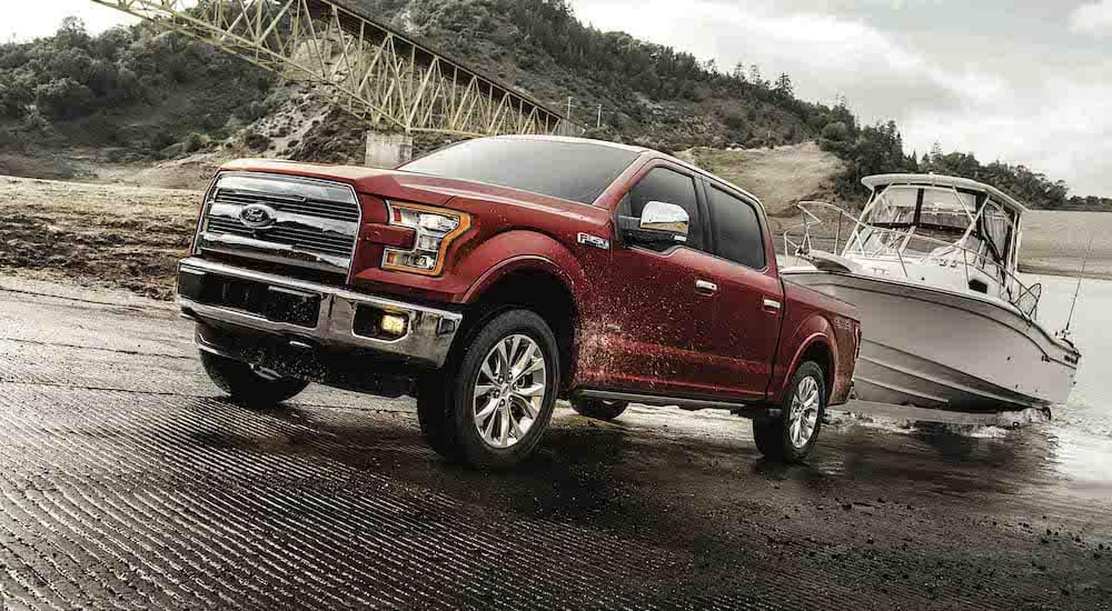 A red 2017 Ford F-150, which is popular among used Ford trucks, is backing a boat into the water near Cincinnati, OH.