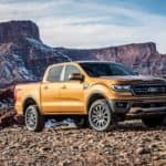 An orange 2019 Ford Ranger is parked in front of rock formations.