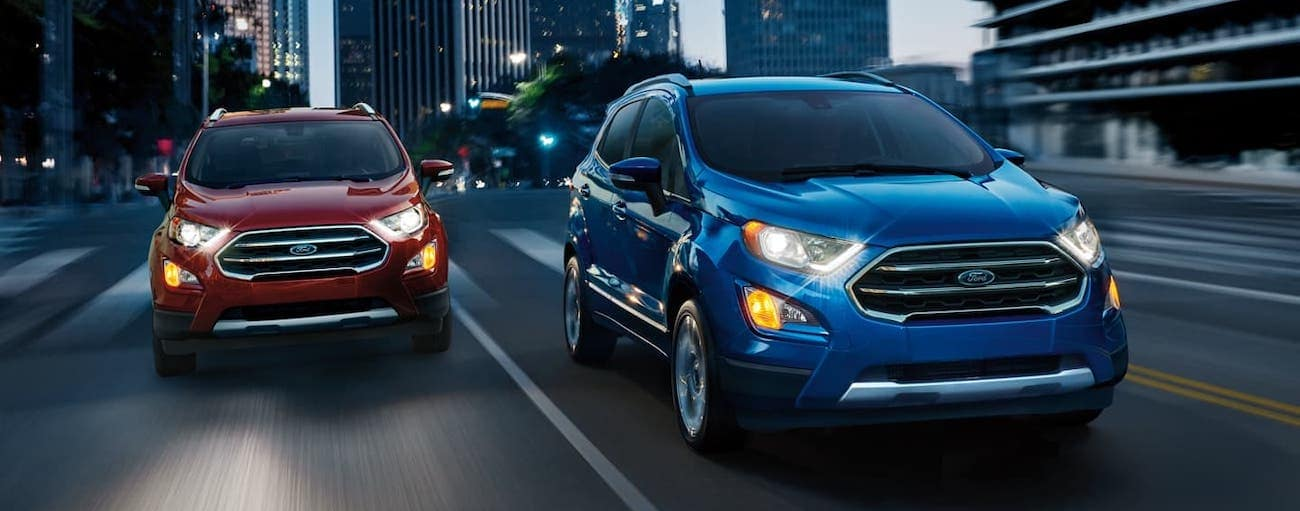 A red and a blue 2020 Ford EcoSport are driving outside Cincinnati, OH, at night.