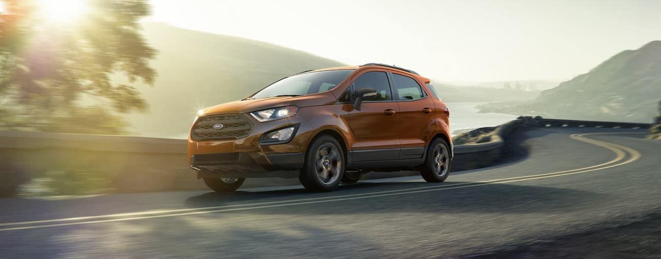 An orange 2020 Ford EcoSport is driving on a highway at dusk.