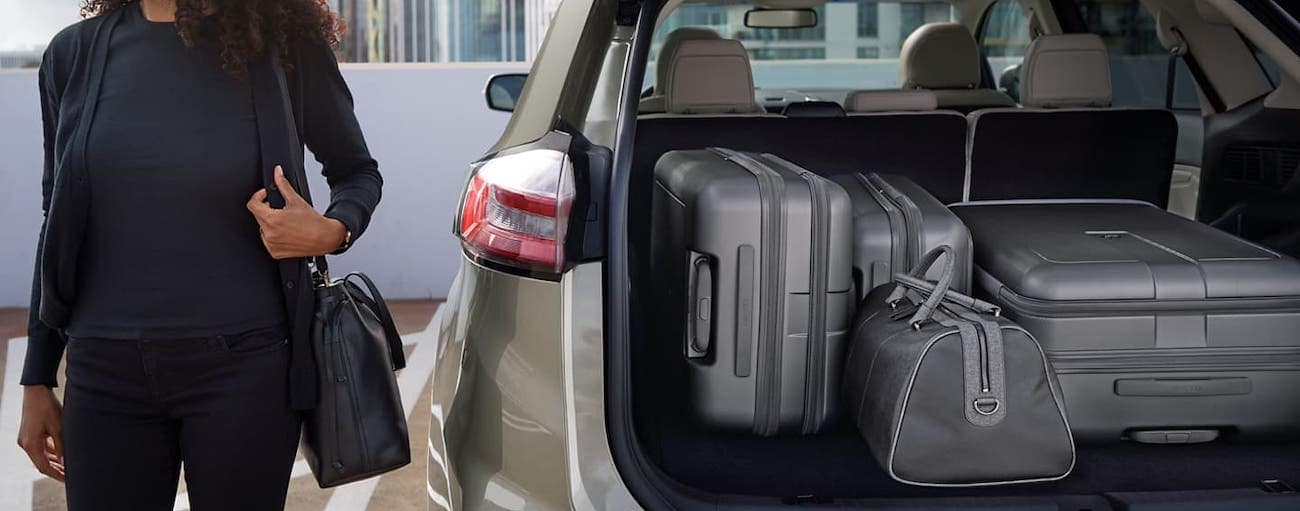 A woman is standing next to the open liftgate of her tan 2020 Ford Edge and there is luggage in the cargo area.
