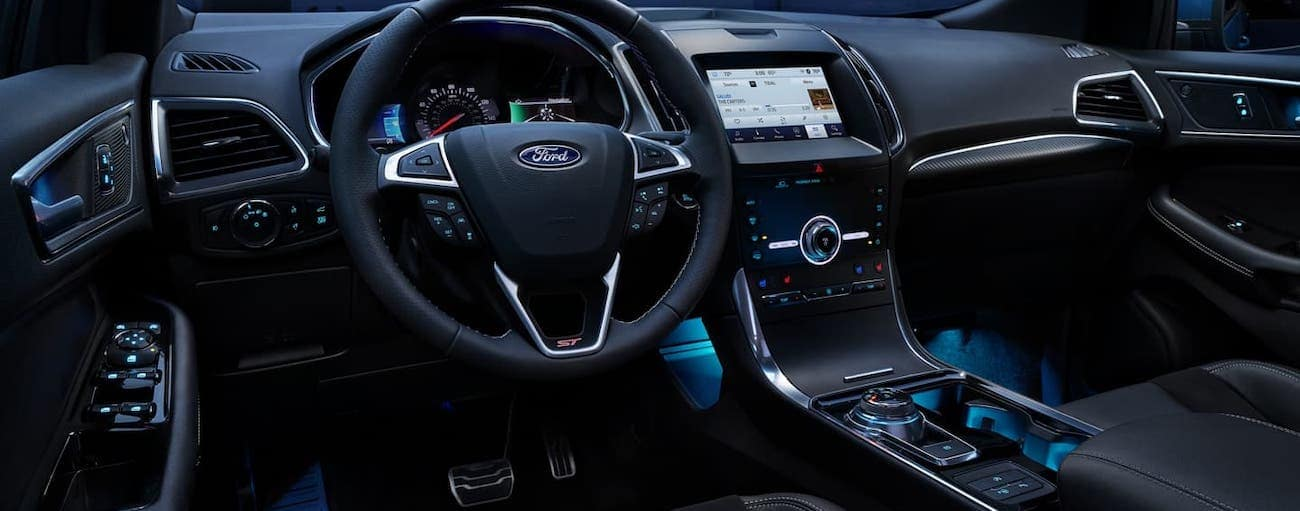 The lit up steering wheel and dashboard is shown of a 2020 Ford Edge at night.