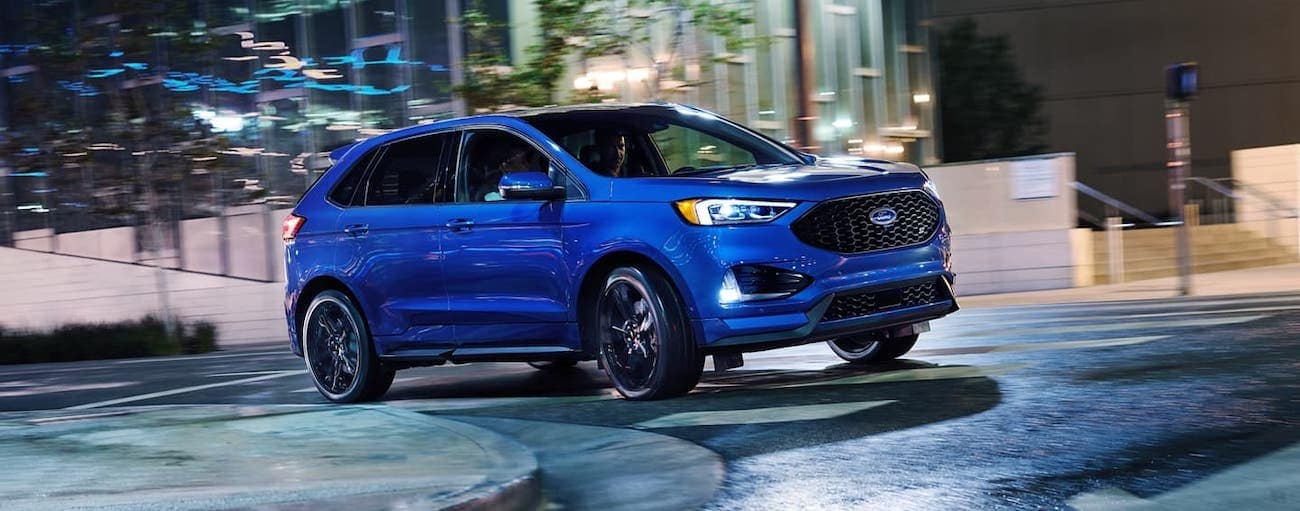 A blue 2020 Ford Edge ST is driving on a Cincinnati, OH, street at night.