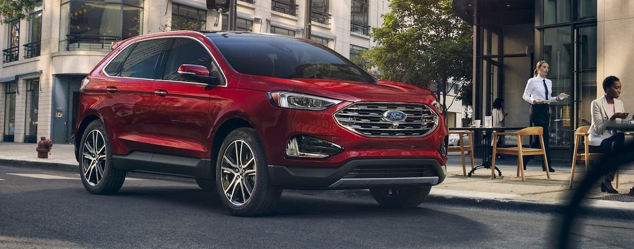 A red 2020 Ford Edge Titanium is driving past a Cincinnati, OH, cafe.