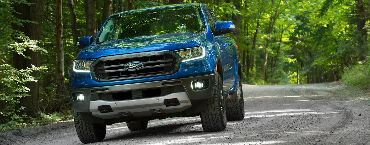 A blue 2020 Ford Ranger is driving on a tree-lined road outside Cincinnati, OH.