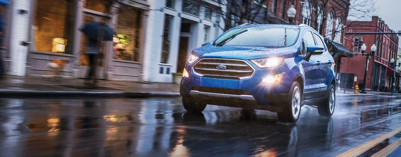 A blue EcoSport is driving in the rain on a Cincinnati, OH, road.