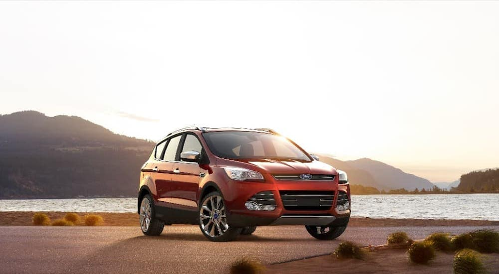 A red 2016 Ford Escape is parked on a beach at sunset.