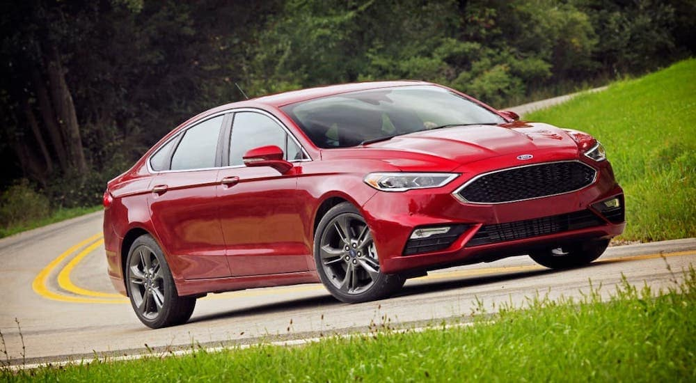 A red 2017 Ford Certified Pre-Owned Fusion is driving on a winding road.
