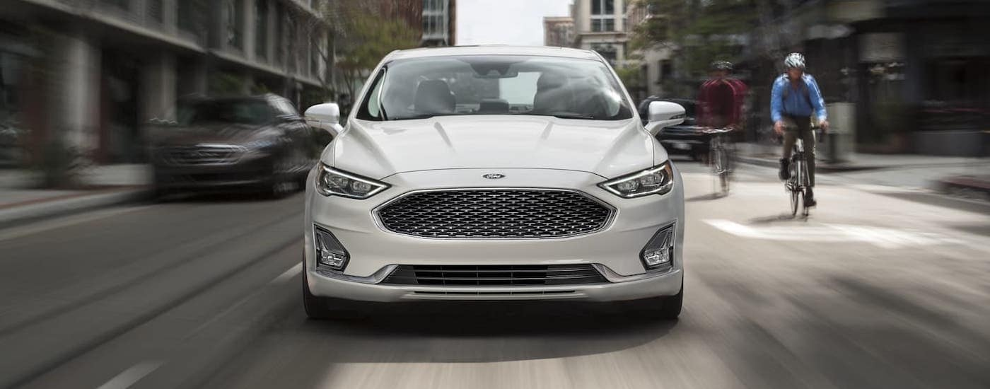 A white 2019 Ford Certified Pre-Owned Fusion is driving through a city, shown from the front next to someone on a bicycle.