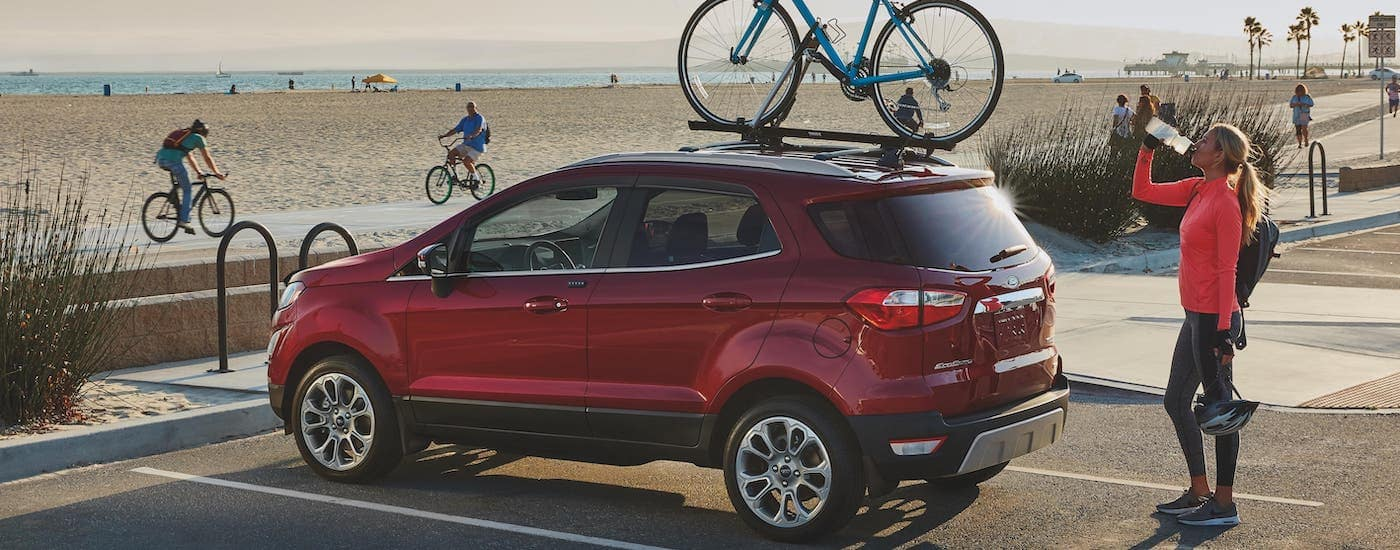 A woman is standing next to a red 2020 Ford EcoSport, winner of the 2020 Ford EcoSport vs 2020 Buick Encore comparison, which is parked at a beach with a bike on the roof.