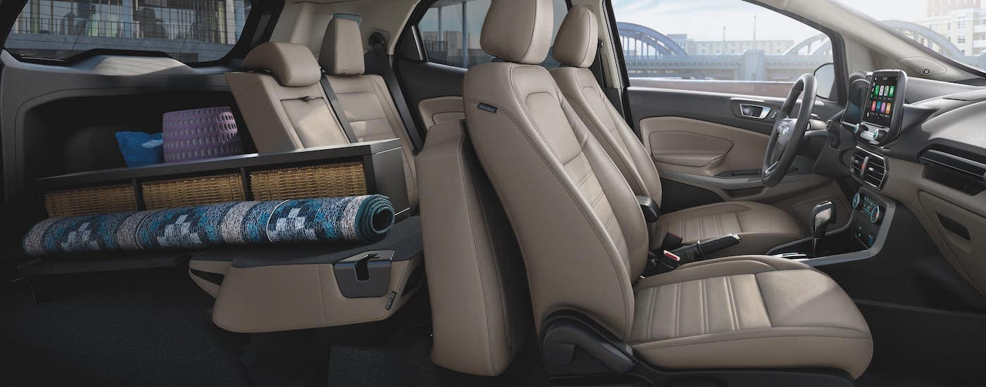 The two rows of seats in a 2020 Ford EcoSport which is parked in Cincinnati, OH, are shown from the side with cargo overflowing into the back seat.