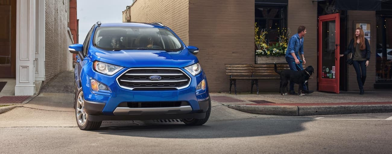 A blue 2020 Ford EcoSport, which wins when comparing the 2020 Ford EcoSport vs 2020 Nissan Kicks, is pulling out of a Cincinnati, OH, side street.