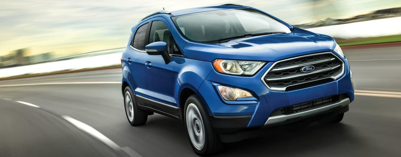 A blue 2020 Ford EcoSport is driving around a bay.