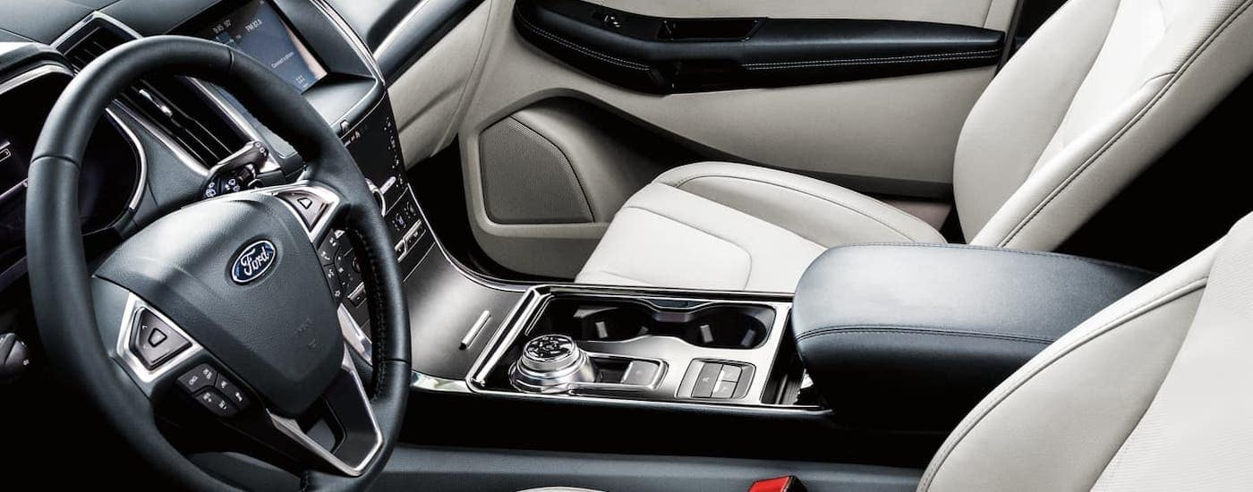 The white and black front seats are shown inside a 2020 Ford Edge Titanium.