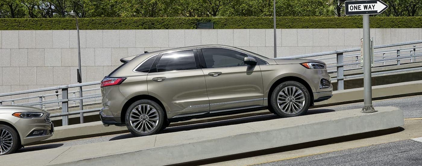 A gold 2020 Ford Edge is parked on a hill and shown from the side.