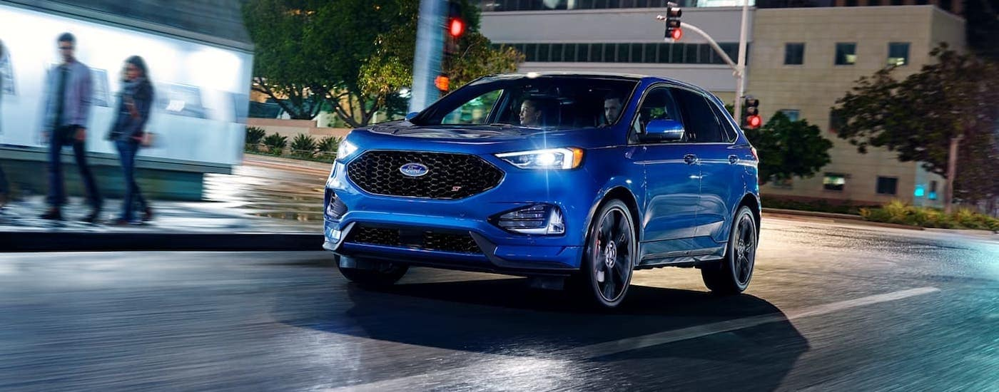 A blue 2020 Ford Edge ST is driving through Cincinnati at night after winning the 2020 Ford Edge vs 2020 Chevy Blazer comparison.