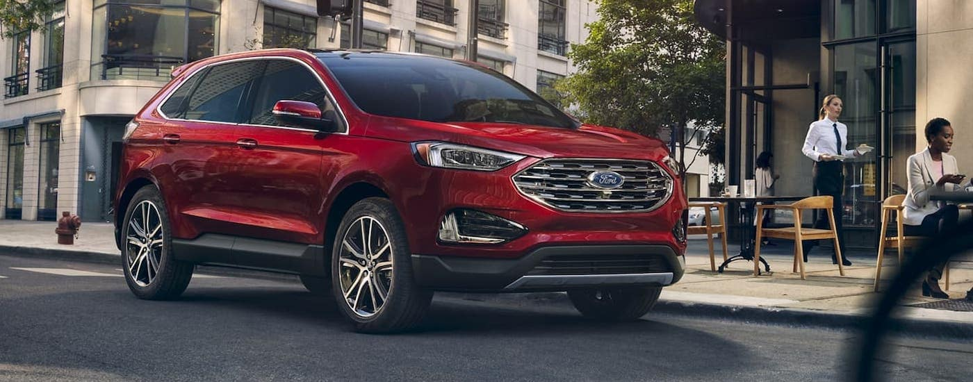 A red 2020 Ford Edge is driving past a restaurant in Cincinnati, OH.