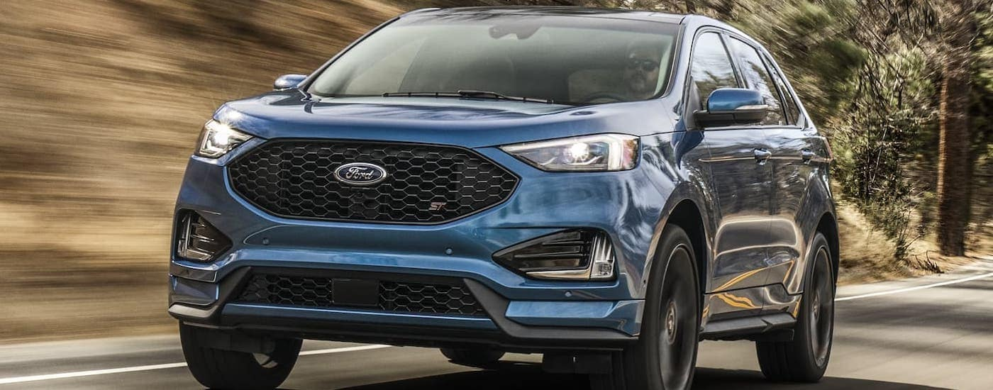 A blue Edge ST is driving on a rural road after winning the 2020 Ford Edge vs 2020 Honda Passport comparison.